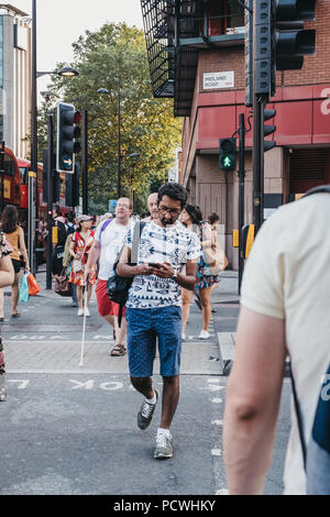Man crossing a road towards King's Cross Station, London, on a zebra crossing while using his phone. - Stock Photo