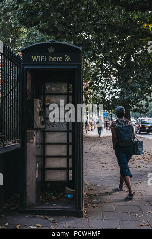 Woman walks past black phone box on Euston Road in London, UK. - Stock Photo