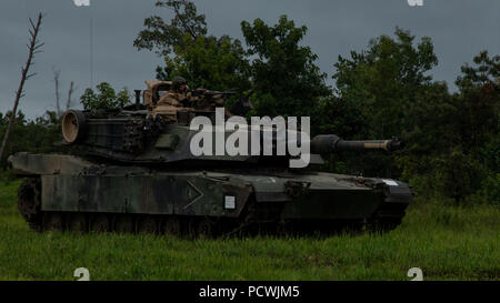 An M1A1 Abrams tank with the 22nd Marine Expeditionary Unit (MEU) provides overwatch during a range as part of the 22nd MEU Deployment for Training at Fort A.P. Hill, VA., July 29, 2018. The training allowed the Marines with Battalion Landing Team, 1st Battalion, 2nd Marines, 22nd MEU to incorporate tanks, amphibious assault vehicles, aircraft, indirect fire, mortars and infantry into a series of combined arms live-fire ranges in order to maintain proficiency for their upcoming deployment. (U.S. Marine Corps photo by Cpl. Aaron Henson) - Stock Photo