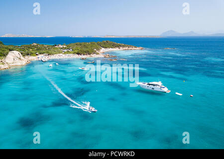 View from above, aerial picture of two boats sailing on a transparent and turquoise Mediterranean sea. Emerald Coast (Costa Smeralda) in Sardinia, Ita - Stock Photo