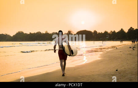 WELIGAMA SRI LANKA - JAN 5, 2017: Unidentified  surfer on sunset at  Weligama beach , Sri Lanka.  It coast of Indian ocean is the best surf paradise i - Stock Photo