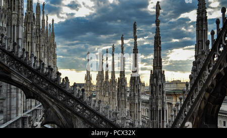 Roof terraces of gothic Milan Cathedral, or Duomo di Milano, at sunset. The beautiful gothic cathedral is the main tourist attraction of Milan - Stock Photo