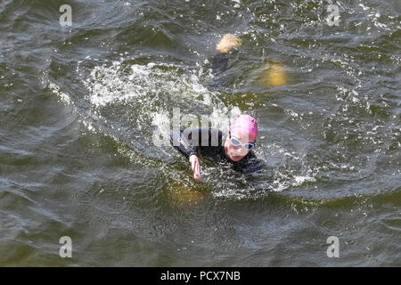 London, UK, 4th August 2018. Athletes compete in the swim part of the route, with the water promising some cooling down from the London heat. Now in its 22nd year, the AJ Bell London Triathlon is the world's largest triathlon, each year welcoming over 13,000 triathletes of all ages and abilities, as well as elite races, to swim, bike and run around the spectacular route. Credit: Imageplotter News and Sports/Alamy Live News - Stock Photo
