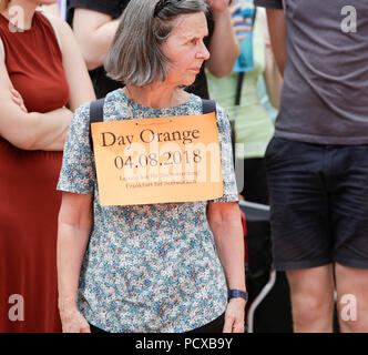 Frankfurt, Germany. 4th August 2018. A protester holds a sign that reads 'Day Orange 04.08.2018 - Ropes away for sea rescue - Frankfurt for Sealift'. Around 100 protesters participated in the DayOrange protest of the Seebrucke (Sealift) movement in Frankfurt in support of sea rescue operations for refugees in the Mediterranean. The protest was part of a German wide day of protest which saw several protests with several thousand people participating. Credit: Michael Debets/Alamy Live News - Stock Photo