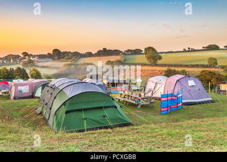 Devon, UK. 5 August 2018.  After a mild cool night, the early morning mist clears as the sun rises over the picturesque little campsite of Broad Park near Bideford in North Devon. Credit: Terry Mathews/Alamy Live News - Stock Photo