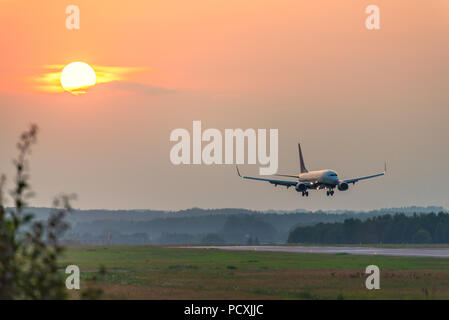 A plane approaches the airport during sunset. - Stock Photo