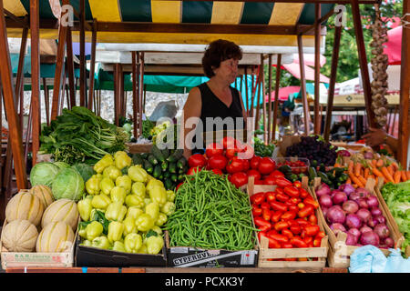 Zadar, Croatia - July 23, 2018: Senior lady selling fruits a vegetables in the market of Zadar old town - Stock Photo