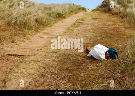 A bag of rubbish left by the boardwalk on the Norfolk Coast Path at Burnham Overy Staithe, Norfolk, England, United Kingdom, Europe. - Stock Photo