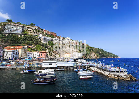 Boats and buildings along the cliffs at Marina Grande in Sorrento, Italy, Campania region on a beautiful day - Stock Photo