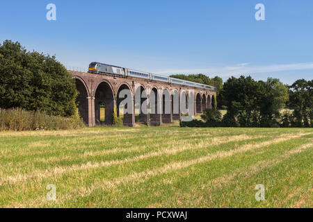 A Chiltern railways class 68 locomotive crossing  Saunderton Viaduct (south of Banbury) with a mainline express train from marylebone - Stock Photo