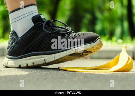 Men's foot in saturated black trainers slides on a yellow peel from banana on the background of summer park. - Stock Photo