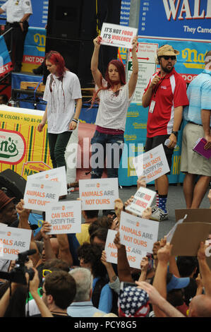 NEW YORK, NY - JULY 04: Matt Stonie eats 62 hot dogs to upset Joey Chestnut as the new winner of the 2015 Nathan's Famous 4th Of July International Hot Dog Eating Contest at Coney Island on July 4, 2015 in New York City   People:  Protesters - Stock Photo