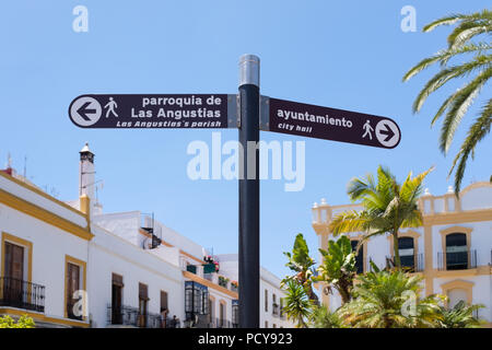Tourist information sign in Ayamonte, Andlaucia, Spain indicating the direction to the city hall, or town hall and the local church. It is written in  - Stock Photo