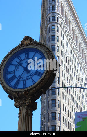 Iconic cast-iron Fifth Avenue Building street clock seen against Flatiron Building, Flatiron District, Manhattan on JULY 5th, 2017 in New York, USA. ( - Stock Photo