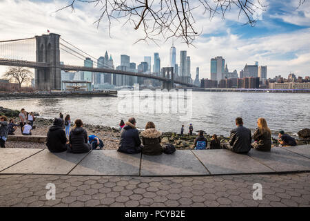People sitting in DUMBO  and enjoying the view of Brooklyn Bridge and Downtown Manhattan in New York Stock Photo