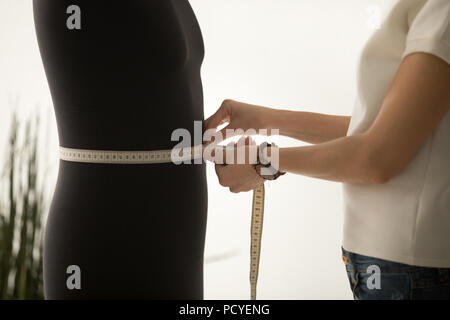 Close up of dressmaker measuring mannequin waist with tape - Stock Photo