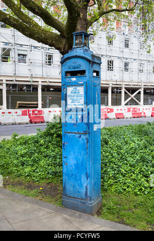 A blue police telephone box in London, UK - Stock Photo