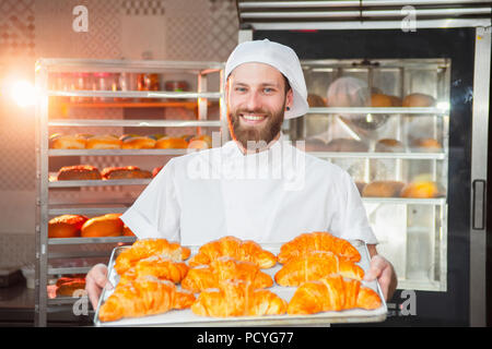 Young handsome baker holding freshly baked croissants in hands on the background of the oven. - Stock Photo