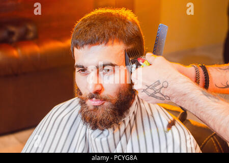 Barber does a haircut on his head with a trimmer to a young handsome guy with a mustache and beard. Men's hair salon. - Stock Photo