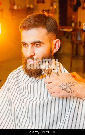 Barber cuts a beard of vintage hair clippers to a young handsome guy with a beard and mustache. Men's hair salon. - Stock Photo