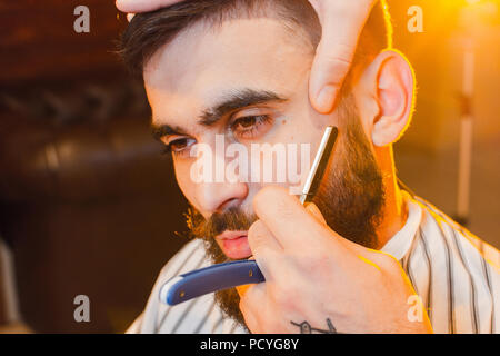 Barber shaves the dangerous razor of a handsome young man with a mustache and beard. Shaving a dangerous razor in a male hairdresser - Stock Photo