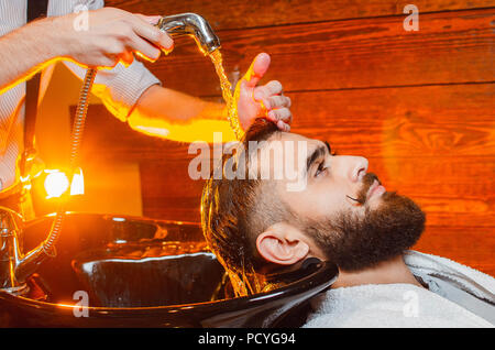 Barber washes the head of a young handsome guy with a beard and mustache in the sink. Male beauty salon. - Stock Photo