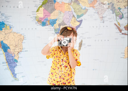 little caucasian boy taking picture with vintage film camera on world map background