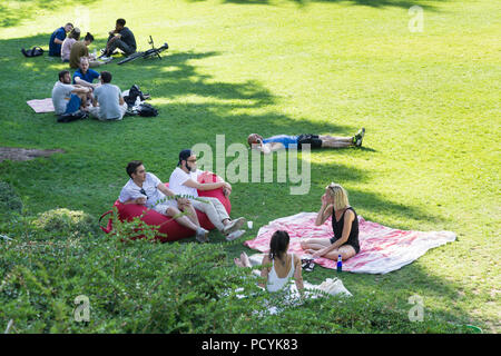 People sitting on the grass, chatting, having a picnic in the park. Promenade Plantee in Paris, France. - Stock Photo