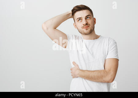 Attractive unshaven sportsman feeling pain in chest touching bone, smirking from painful feeling spraining mascule during workout in gym raising and h - Stock Photo