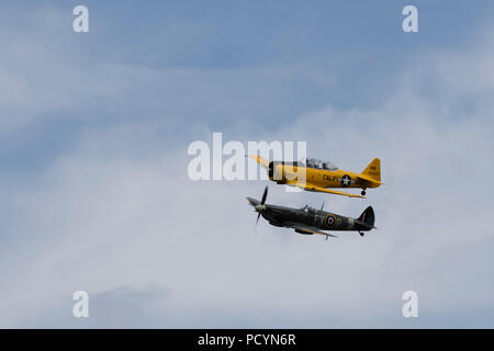 A Spitfire and North American Aviation T-6 Texan Harvard in flight side by side - Stock Photo