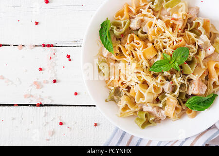 Creamy pasta with chicken and eggplant  served in deep plate. Italian food. Top view. Flat lay. - Stock Photo