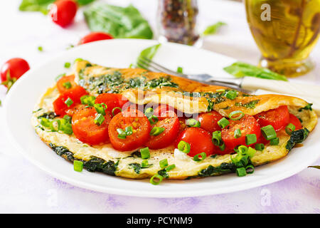 Omelette with tomatoes, spinach and green onion on white plate.  Frittata - italian omelet. - Stock Photo