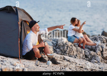 Man sitting on rocky beach looking at sunset, wife and daughter sitting near. - Stock Photo