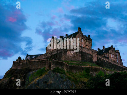 Edinburgh Castle rock at dusk sunset with dark blue sky and pink clouds, Edinburgh, Scotland, UK - Stock Photo