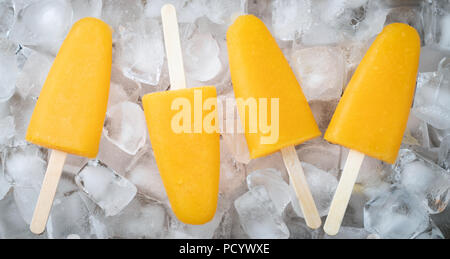 Orange popsicles with juice on a icecubes. Ice pops, flat lay, top view. - Stock Photo