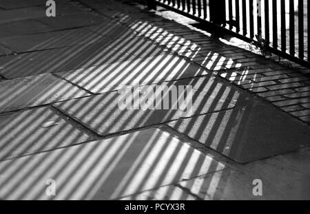 Shadow of a fence on pavement in Edinburgh Scotland - Stock Photo