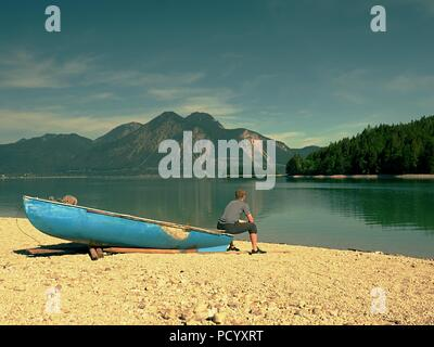 Adult man in blue shirt at old fishing paddle boat at mountains lake coast. Sunny spring day. - Stock Photo