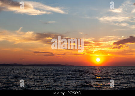 Zadar, Croatia - July 23, 2018: Sunset over the island of Ugljan seen from Zadar - Stock Photo