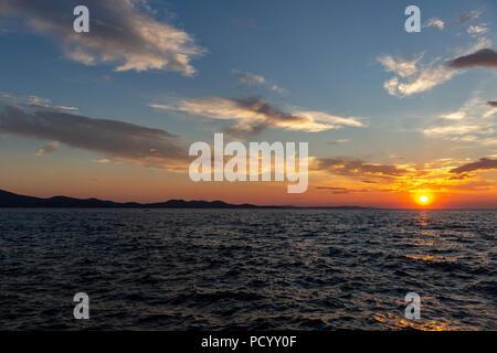 Zadar, Croatia - July 23, 2018: Dusk over the island of Ugljan seen from Zadar - Stock Photo