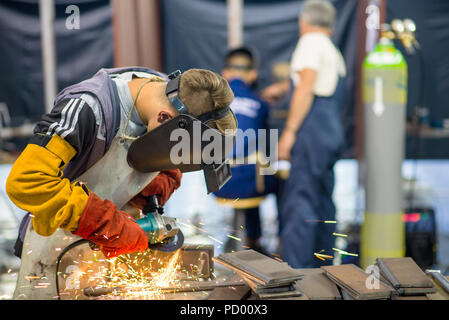 Belgrade, Serbia - May 23, 2018: Welder working in a factory with two blurry workers in the background - Stock Photo