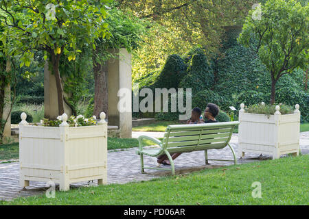 A couple sitting on bench in the Park Bercy in the 13th arrondissement of Paris, France. - Stock Photo