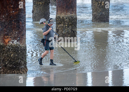 Man with metal detector beneath the St. Johns County Ocean Pier at St. Augustine Beach, Florida. (USA) - Stock Photo
