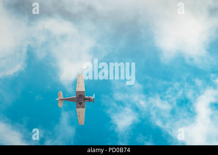 Aerobatic airplane flying high in blue sky viewed from the ground - Stock Photo