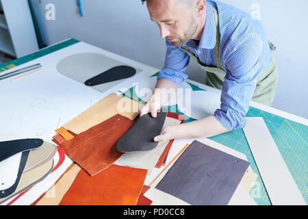 Shoemaker working at workshop - Stock Photo