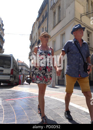 Two people walking hand in hand in Montpellier, France - Stock Photo