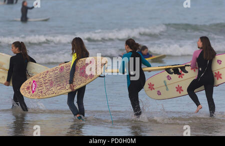 female surfers or surf chicks dressed in wetsuits carrying surfboards at the waters edge on a beach walking into the water to surf in Muizenberg - Stock Photo
