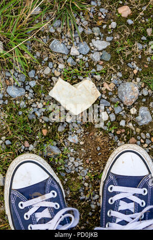 Top view of heart shaped white marble stone found on the ground and partial dirty blue sneakers with white laces, Vitosha mountain near Sofia, Bulgaria in pleasant summer afternoon - Stock Photo