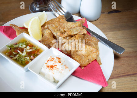 An English pub/restaurant entree dish of Roast Chicken skin with Paprika mayonnaise and Garlic and tomato salsa dips garnished with fresh lemon wedge - Stock Photo