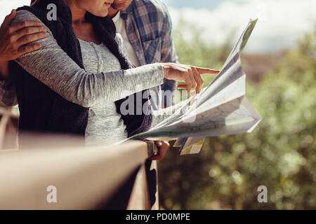 Woman pointing at the map while standing with her boyfriend. Couple looking for travel destination on map. - Stock Photo