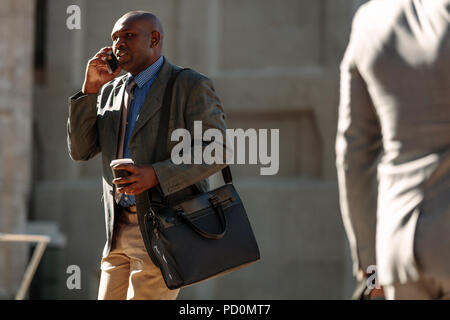 Businessman commuting to office talking over mobile phone with a coffee cup in hand with sun flare in the background. Busy man walking to office carry - Stock Photo